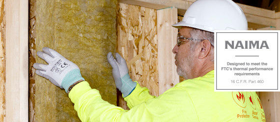 Man in yellow sweater installs insulation