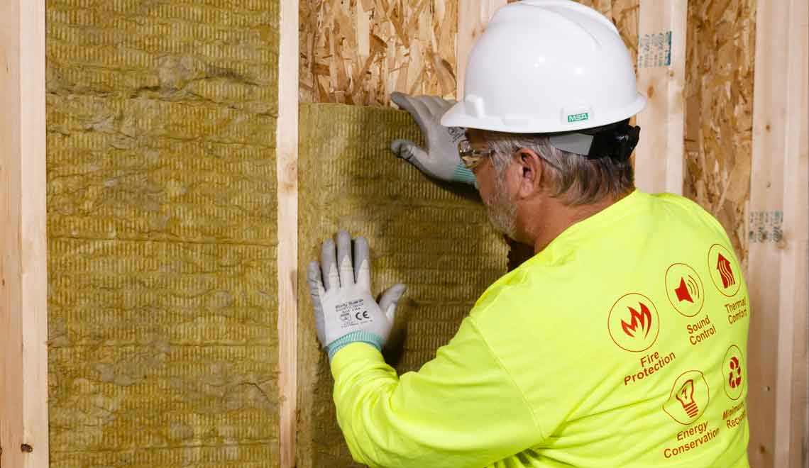 A worker installs ThermaFiber mineral wool insulation