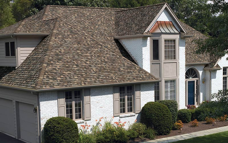 A white brick house shows off the dynamic color of Sand Dune light brown shingles paired with warm tan window shutters.